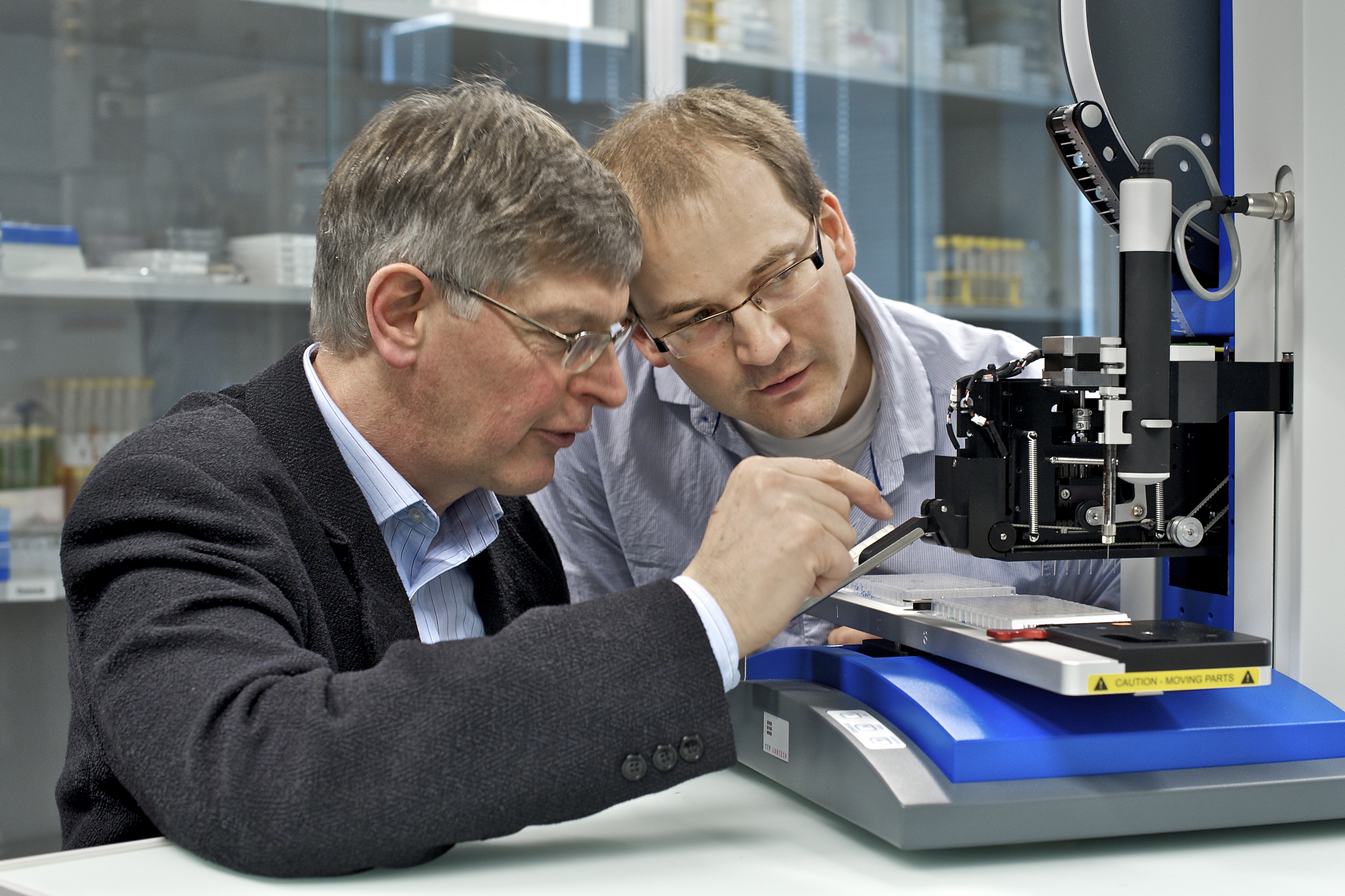 "PSI researchers Gebhard Schertler and Jörg Standfuss adjusting a ""robot"" that can produce protein crystals needed for the determination of protein structures. (Photo: PSI/M.Fischer)"
