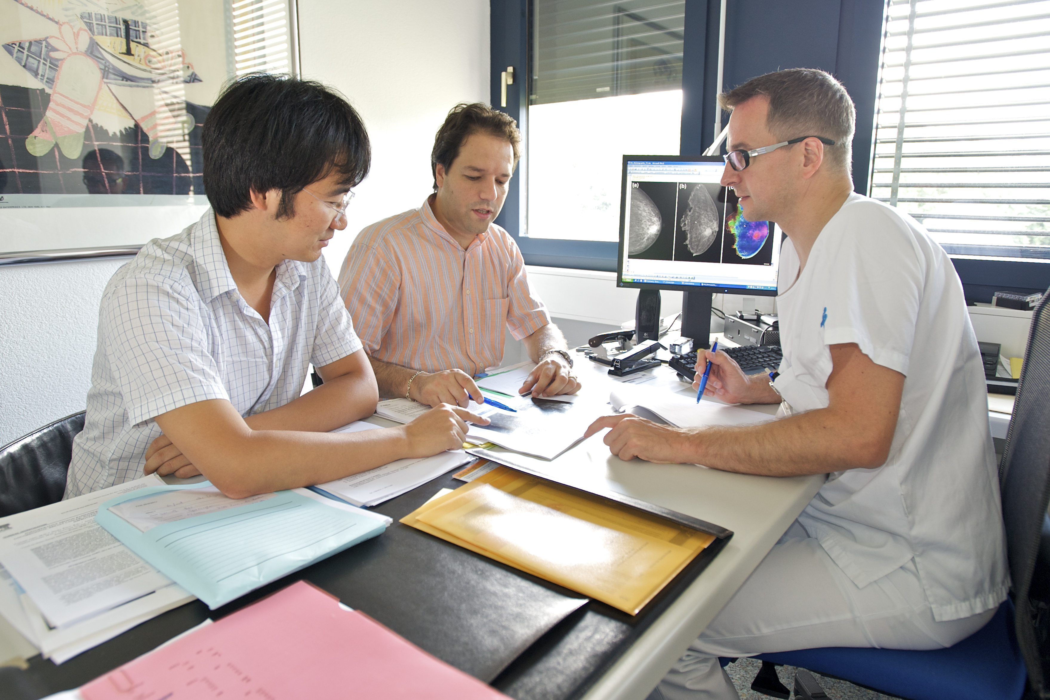 Prof. Dr. M. Stampanoni (centre) and Dr. Nik Hauser (right) discuss the results of the innovative mammography procedure with Dr. Zhentian Wang (left), who carried out the investigations at PSI. (PSI/M.Fischer)