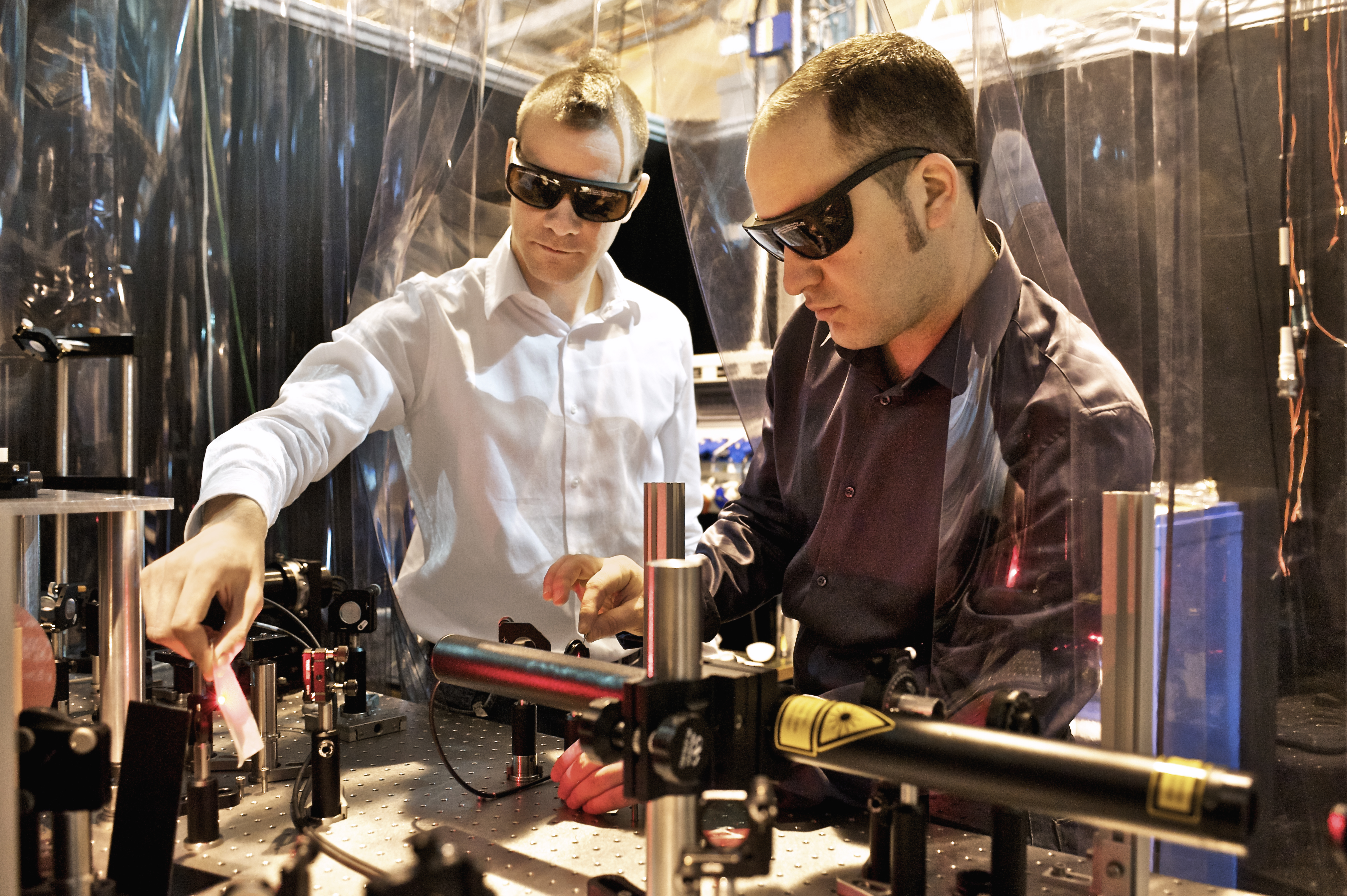 PSI scientists Loïc Le Guyader (left) and Souliman El Moussaoui adjusting the laser that was used to heat the magnetic sample. (Paul Scherrer Institute/M. Fischer)