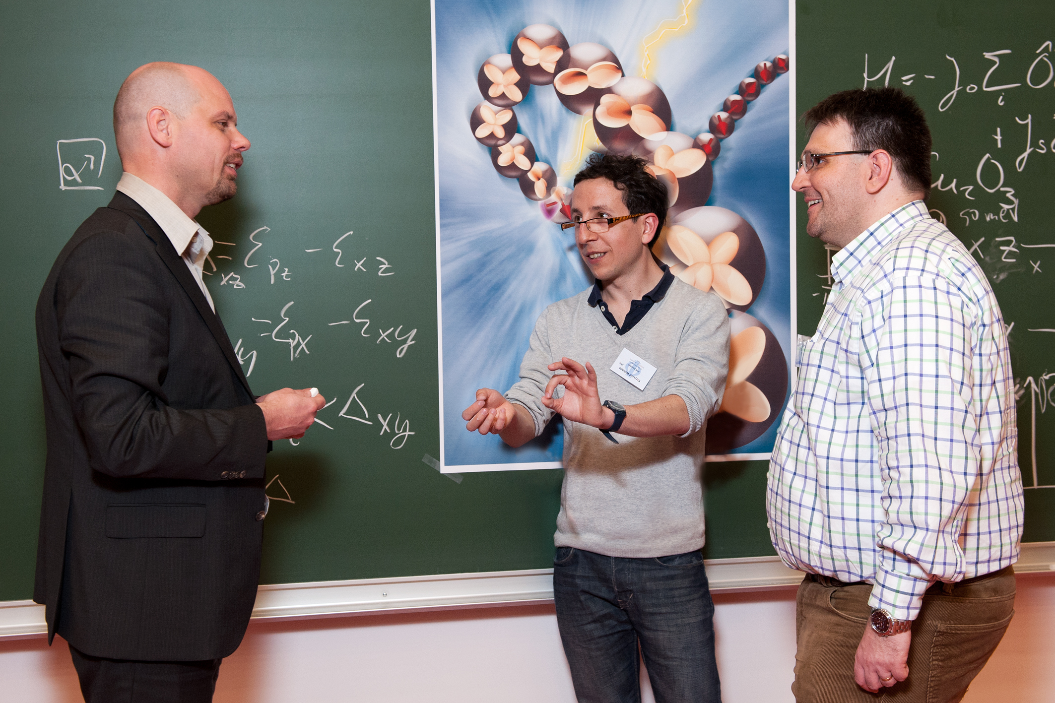 Jeroen van den Brink (left) und Krzysztof Wohlfeld (centre), both from the IFW Dresden, discussing the theoretical description of the experimental results with PSI researcher Thorsten Schmitt. (Photo: Philip Dera)