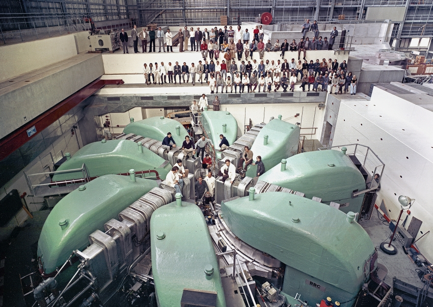 Like on a dinosaur's back. In 1973 just before the proton facility went into service, the team had their picture taken at the large ring cyclotron. (Photo: Paul Scherrer Institute)