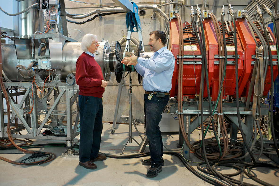 The steel pipe that conducts the muons to the experiment where Stefan Ritt and his colleagues search for a specific, extremely rare muon decay. The DRS4 microchip was developed for this experiment. The photo shows two of the PSI researchers involved: Peter-Raymond Kettle (left) and Stefan Ritt. (Photo: Paul Scherrer Institute/Markus Fischer)