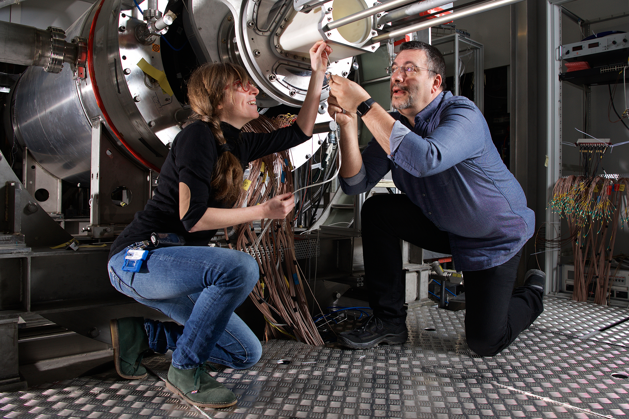 The PSI-scientists Angela Papa and Stefan Ritt at the MEG experiment. A lot of cables are necessary to read out the many particle detectors. With these, the scientists analyse all of the detected particle decays in the search for the special MEG decay. (Photo: Paul Scherrer Institute/Markus Fischer)