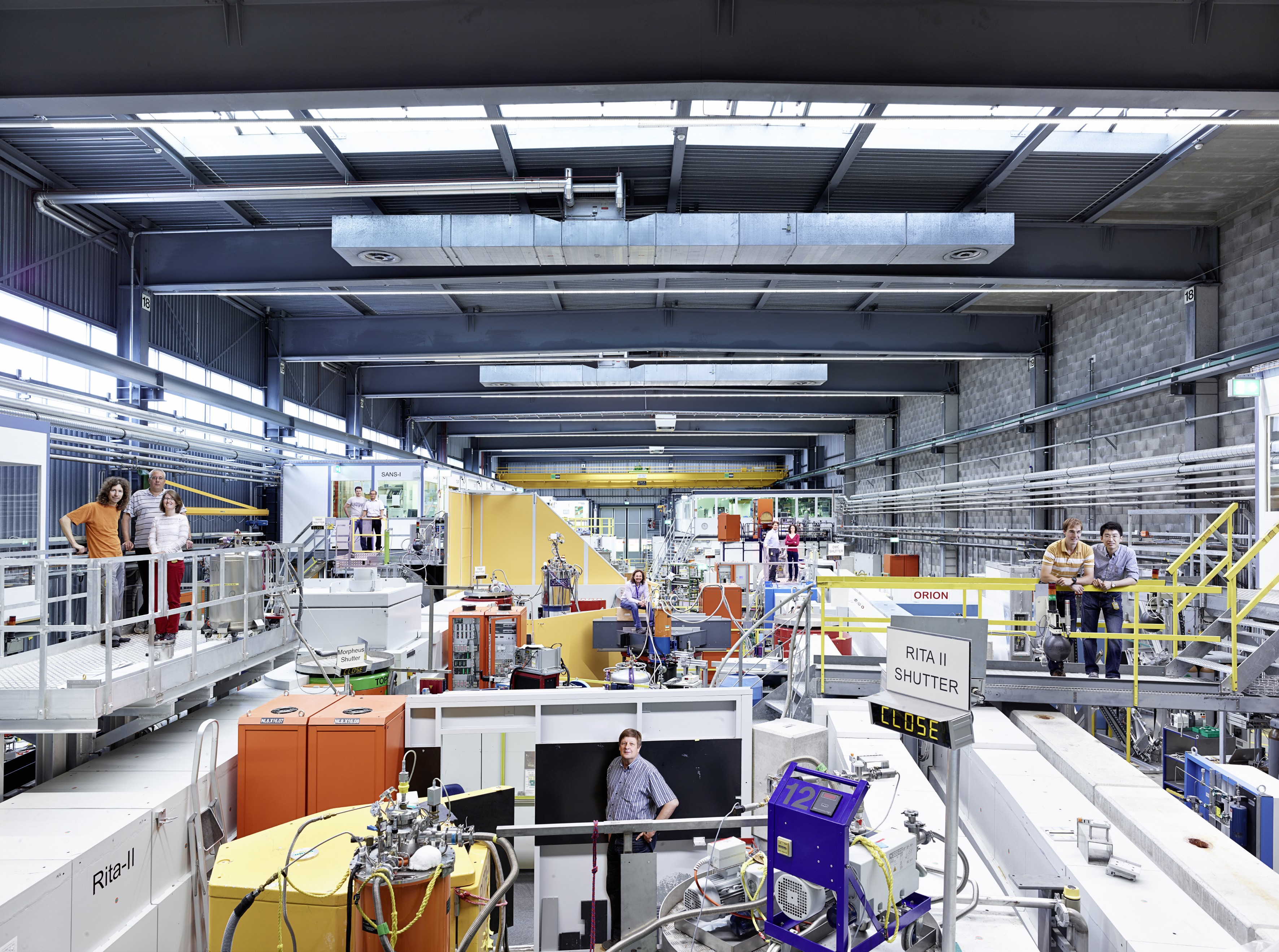 View into a part of the hall where experiments with neutrons are carried out at the Paul Scherrer Institute PSI. The photo is taken from the viewpoint of the neutron source. You can see some of the individual experimental setups, which are distributed throughout the hall. Inside the concrete channels are neutron guides, which lead neutrons to the experiment stations at the end of the hall. (Photo: Scanderbeg Sauer Photography)