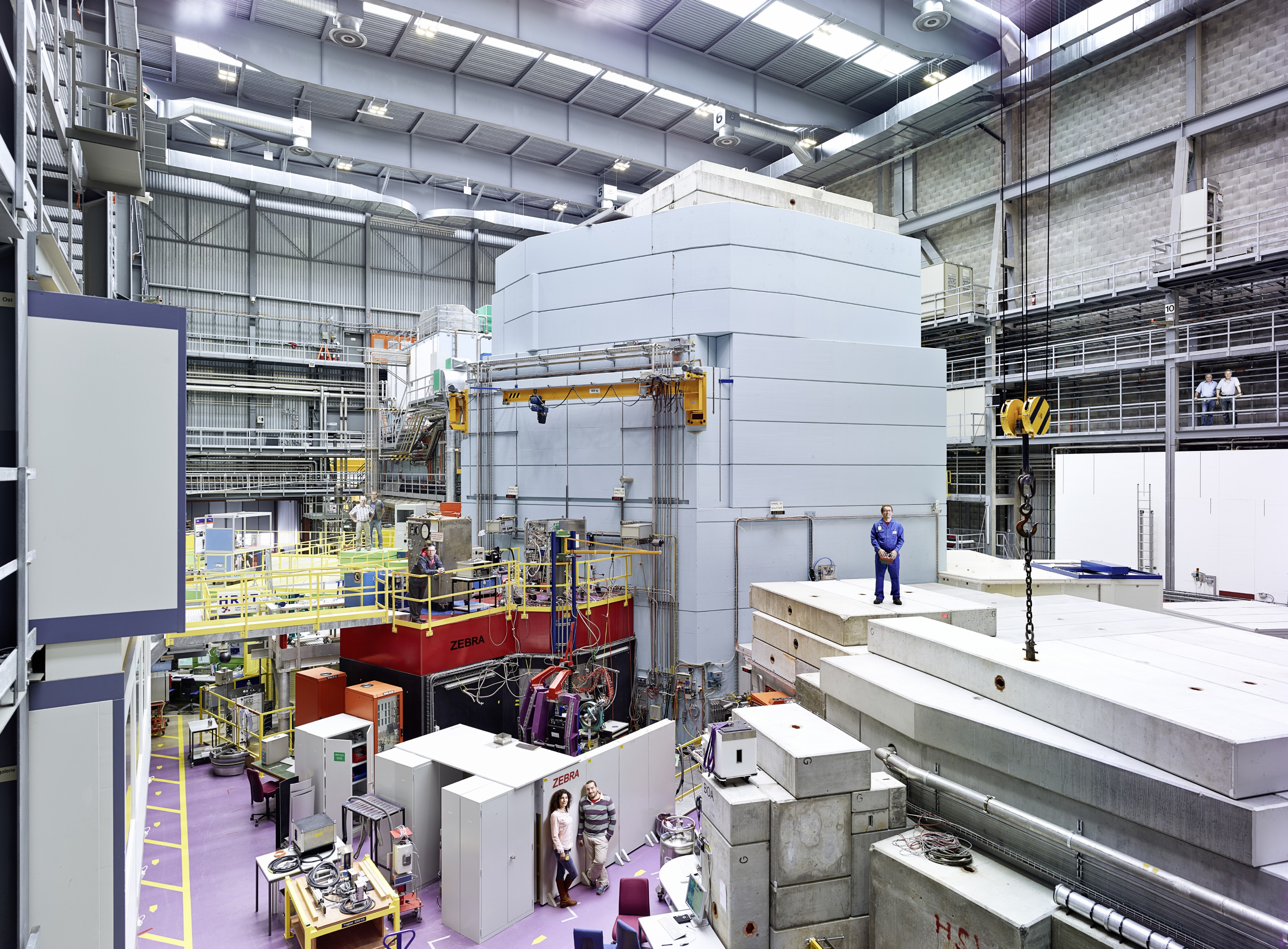 Part of the experiment hall at the Swiss Spallation Neutron Source SINQ of the Paul Scherrer Institute PSI. Plainly visible in the middle of the picture is a light-blue steel and concrete structure: the neutron source. Inside it there is a water-filled container and within that, in turn, sits a block of metal from which a beam of fast protons knocks out neutrons for the experiments. Experiment stations are arranged around this neutron source. (Photo: Scanderbeg Sauer Photography)