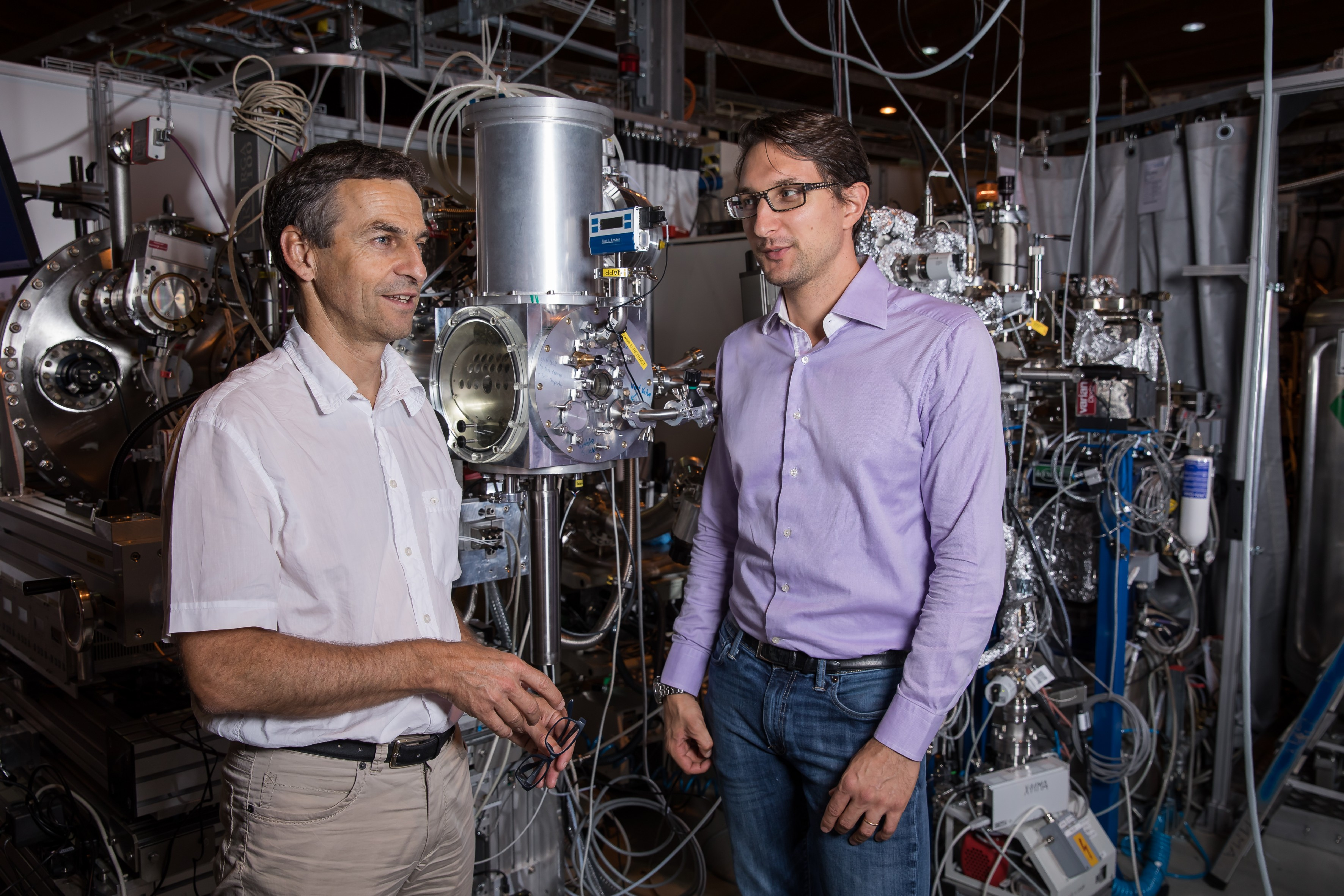 PSI researchers Markus Ammann (left) and Luca Artiglia at the experiment chamber they developed, which enabled them to recreate and capture processes as they occur in Earth's atmosphere with unprecedented precision. (Photo: Paul Scherrer Institute/Mahir Dzambegovic)