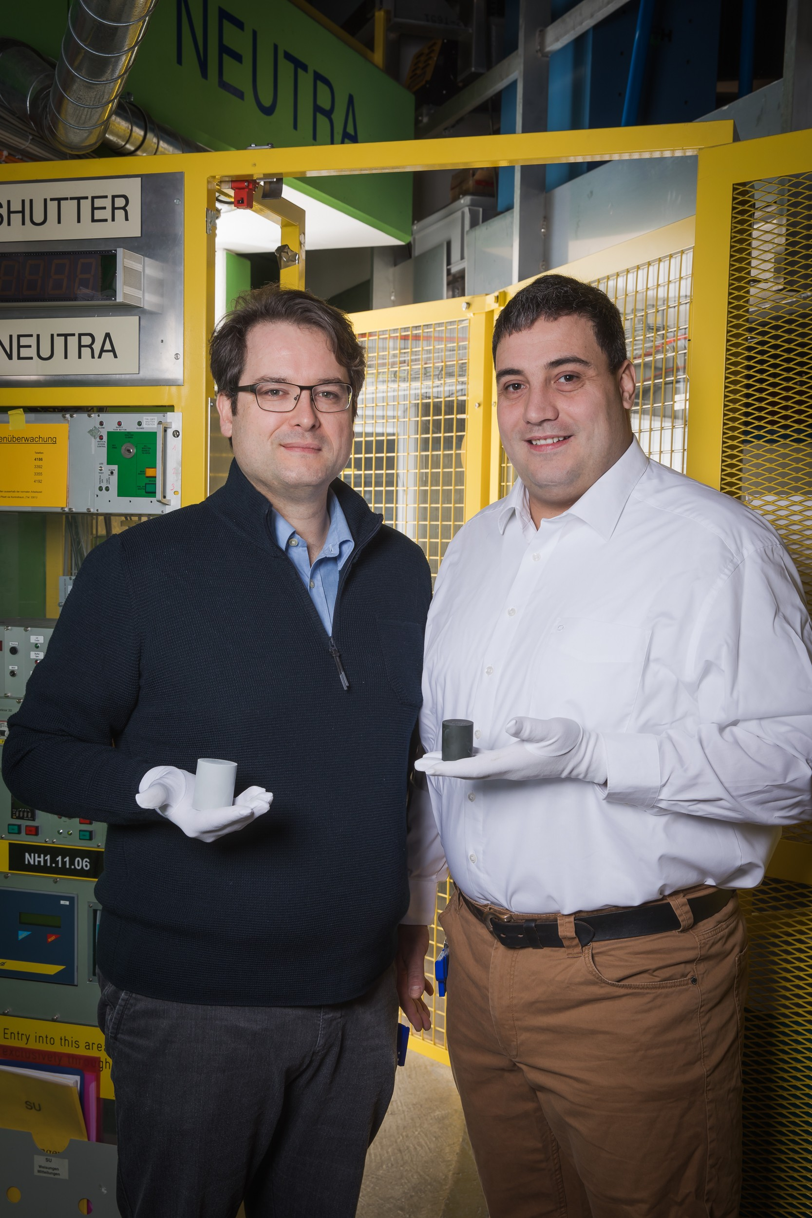 PSI researchers David Mannes (left) and Christian Grünzweig in front of the experiment station NEUTRA. This is where they produced the neutron images of ceramic components made by the technology company ABB. Each of the researchers is holding one of the different types of these ceramic varistors: the light-coloured one on the left has not been fired yet; the dark one on the right already has. (Photo: Paul Scherrer Institute/Mahir Dzambegovic)