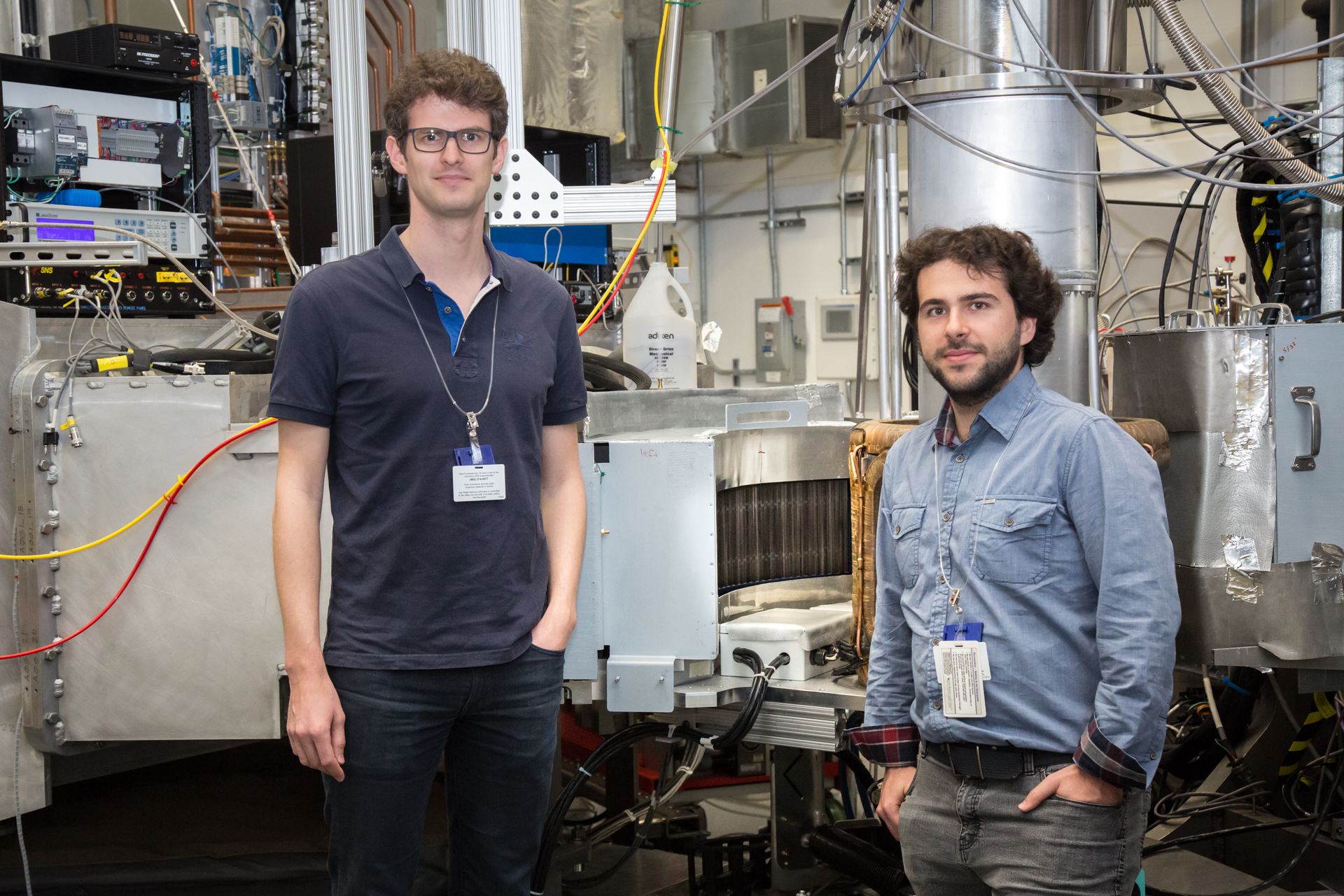 NUM researchers Romain Sibille (left) and Nicolas Gauthier at Oak Ridge National Laboratory (US), in front of the HYSPEC spectrometer, and its polarization analyser designed and built at PSI. The spectrometer has been instrumental in their study of the quantum spin ice Pr<sub>2</sub>Hf<sub>2</sub>O<sub>7</sub>.<br>(Image credit: ORNL/Genevieve Martin)