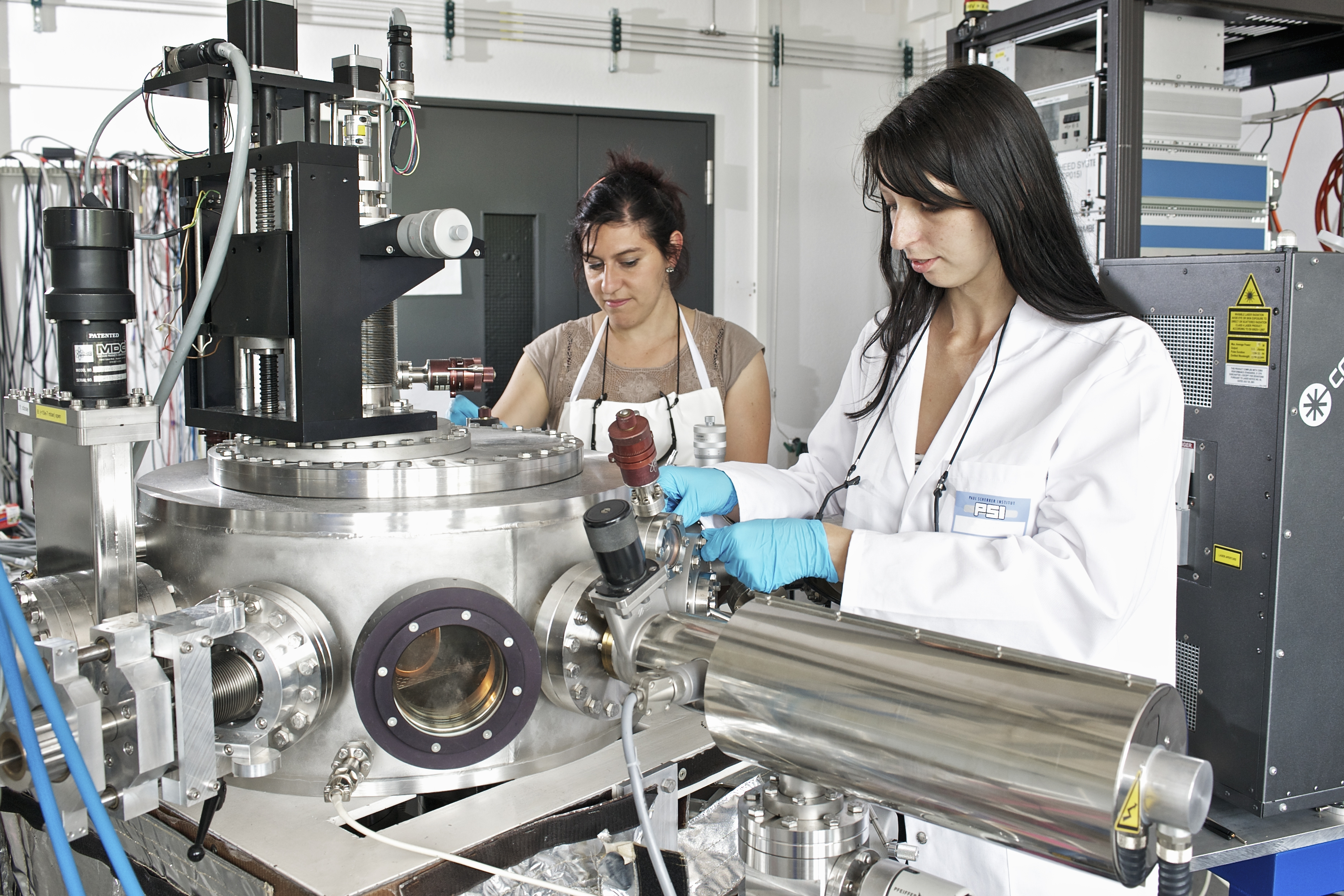 The researchers Claudia Cancellieri (left) and Mathilde Reinle-Schmitt at an apparatus that produces thin layers of different materials with the aid of a laser (Paul Scherrer Institute/M. Fischer)
