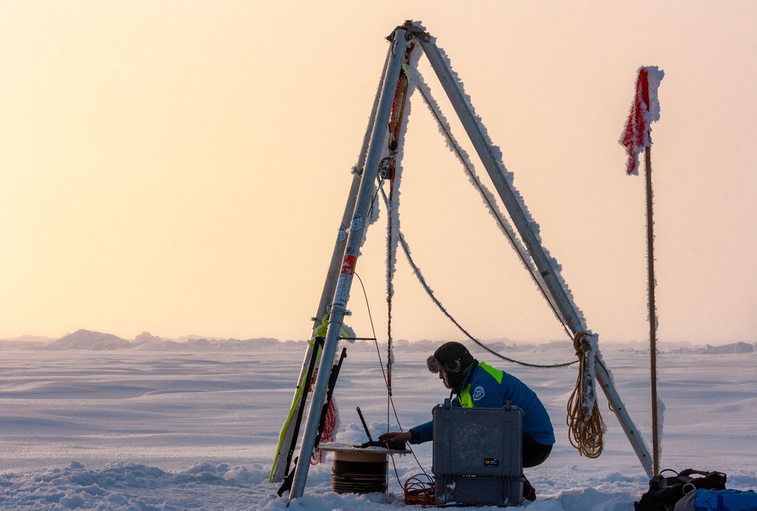 A researcher setting up a measurement station in the Arctic