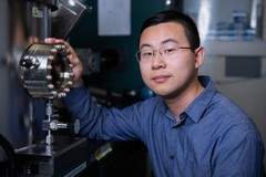 Zhaochu Luo, lead author of the study, in front of a so-called sputter deposition tool. In the apparatus the layers of platinum, cobalt and aluminium oxide are produced. Each layer is only a few nanometers thick. (Photo: Paul Scherrer Institute/Mahir Dzambegovic)