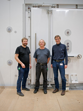 Georg Bison (left), Bernhard Lauss (center), and Klaus Kirch in front of the door to the shielding room.