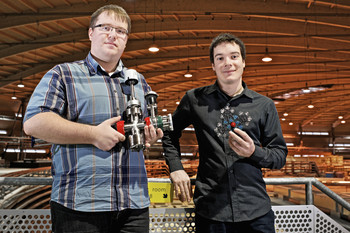"The PSI researchers Jan Nowakowski (left) and Christian Wäckerlin in the Swiss Light Source (SLS) hall. Nowakowski is holding a ""vacuum suitcase"", in which samples to be studied are transported to SLS, and Wäckerlin holds the model of one of the molecules used. (Photo: Paul Scherrer Institut/Markus Fischer)"