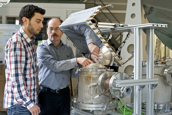 The researchers Christian Wieckert and Nikolaos Tzouganatos during work at the solar reactor. Photo: Paul Scherrer Institute/Markus Fischer.