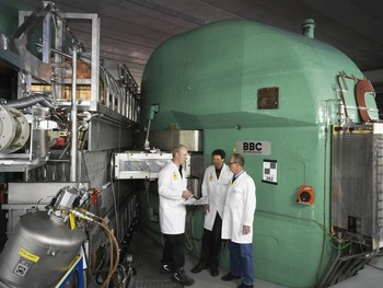 Three lofty men beside an even bigger magnet of the ring cyclotron. In the middle is Joachim Grillenberger, and on his right his predecessor Stefan Adam. On the left in the photo is one of the four cavities which accelerate the protons on their circular trajectory. (Photo: Scanderbeg Sauer Photography)