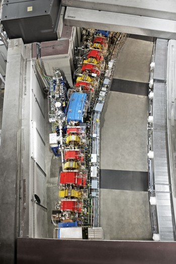 Part of the accelerator facility of the SLS. The beam tube through which the accelerated electrons are moving is almost completely surrounded by magnets (in blue, red and yellow) that both steer and shape the beam.