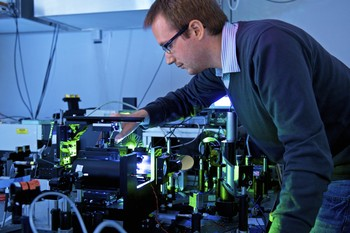 Doctoral Student Richard Geiger investigating the new material in a laser lab at the Paul Scherrer Institute. (Photo: PSI/Markus Fischer)