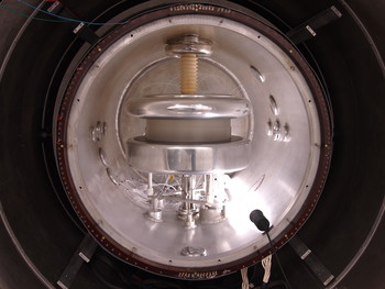 View of the spectrometer which measures the neutron electric dipole moment. The diameter of the silver aluminum tank is one metre. The dark region surrounding it contains a magnetic shield which attenuates the earth's magnetic field by a factor of 10.000. (Photo: PSI/Zema Chowdhuri)