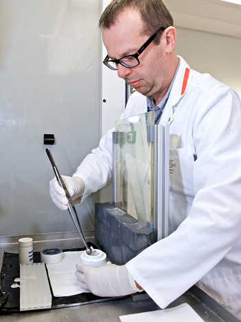 The utmost care is always called for when handling radioactive materials: Martin Béhé working behind radiation shielding glass and lead blocks as he removes the radionuclide lutetium-177 from a small lead container to couple it to a target molecule. (Photo: Paul Scherrer Institute/Markus Fischer)