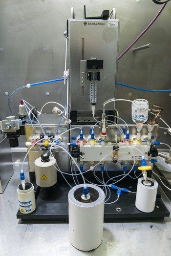 View into the inside of a hot cell in which stands a synthesis apparatus for radioactive medicine. For radiation protection, the vials with the radioactive precursor as well as the product and the waste from the synthesis are kept in lead containers. (Photo: Paul Scherrer Institute/Mahir Dzambegovic)