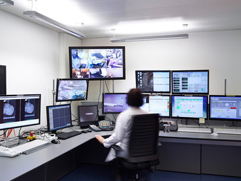 In the control room, all important information from the irradiation device Gantry 2 is displayed on several monitors. Video cameras in the treatment room transmit the current position of the device and observe the patient. This ensures that the proton therapy proceeds precisely according to the treatment plan. (Photo: Scanderbeg Sauer Photography)