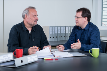 Gerhard Aigner (right), who is responsible for safety and quality management at the Centre for Proton Therapy, keeps track of the 350 plus safety tests carried out each year. Here he discusses the results of a recent test with physicist Martin Grossmann. (Photo: Paul Scherrer Institute/Mahir Dzambegovic)