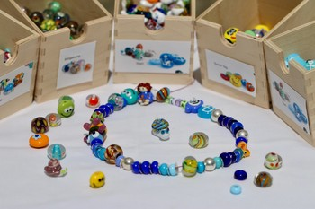 During proton treatment, every child is rewarded with a gift: a necklace of glass beads bearing the child's name. The necklace grows as treatment progresses, with a new hand-made bead added for every irradiation session or medical examination. (Photo: Paul Scherrer Institute/Manuela Reisinger)