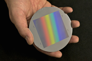 Figure 1: One of the gratings with fine lines in the micrometer range manufactured at PSI as used in the neutrons grating interferometer. The wafer has a diameter of 100 mm. The grid area is 64 x 64 mm2. The rainbow is caused by the refraction of light at the fine structures of the grating.