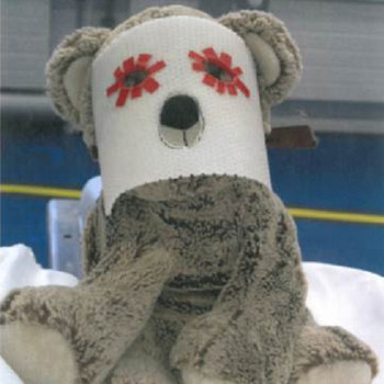 A Teddy bear with a treatment mask